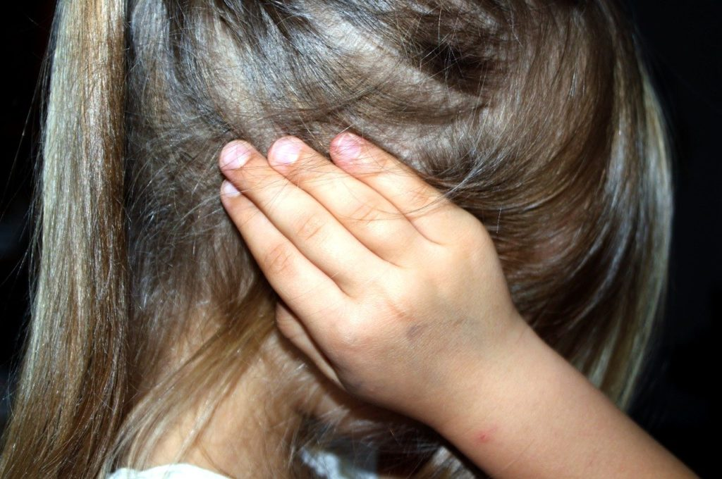 Autistic child covering her ears, CBD oil for autism.