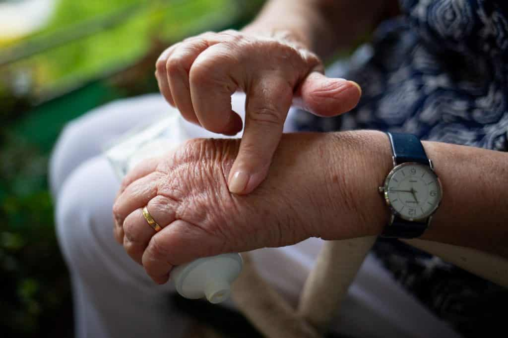An elderly person's hands, using CBD oil on their skin.