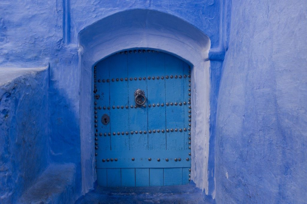 Blue wooden door in a blue stone wall. Microdosing ayahuasca to treat depression.