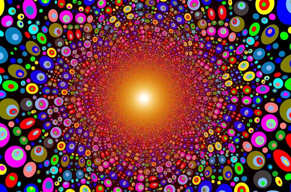 bright light in the center of a tunnel of multicolored dots